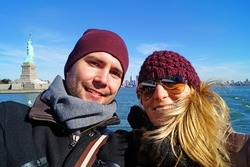 Young couple on a boat in New York. In Background statue of liberty
