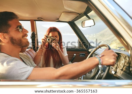 Young couple on a road trip. man driving car with woman taking pictures with retro camera.
