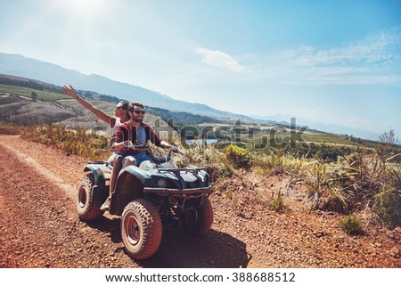 Young couple on an off road adventure. Man driving quad bike with girlfriend sitting behind and enjoying the ride in nature. Stock photo ©