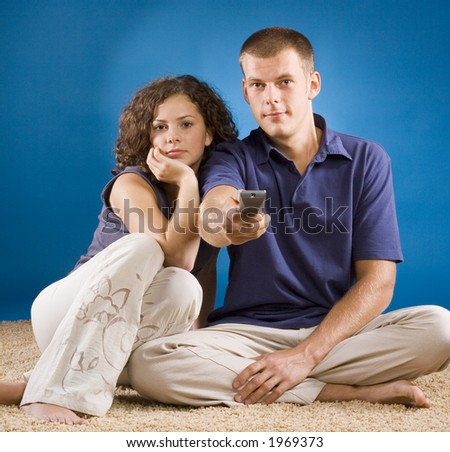 young couple on beige carpet with remote control