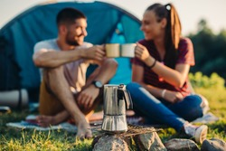 young couple on camping by the river , making a toast with coffee or tea