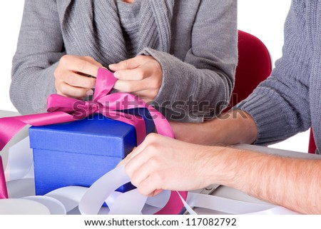 young couple on christmas eve wrapping gift