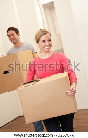 Young couple on moving day carrying cardboard boxes