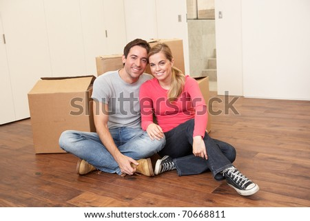 Young couple on moving day sitting with cardboard boxes - stock photo