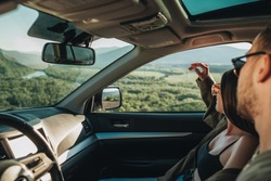 Young Couple on Road Trip, Man Diving Car with Woman Sitting on Passenger Seat