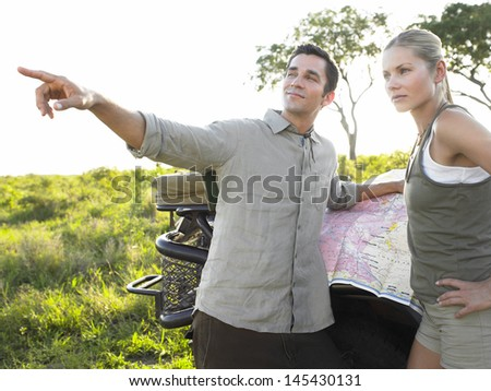 Young couple on safari with map while man pointing away