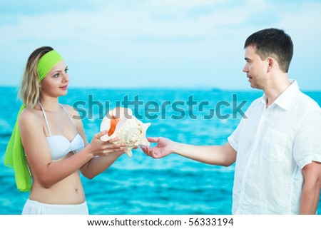 Young couple on the beach holding seashell - stock photo
