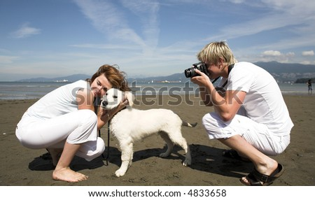 young couple on the beach with dog in taking pictures