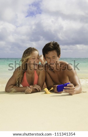 young couple on the beach with their cell phone