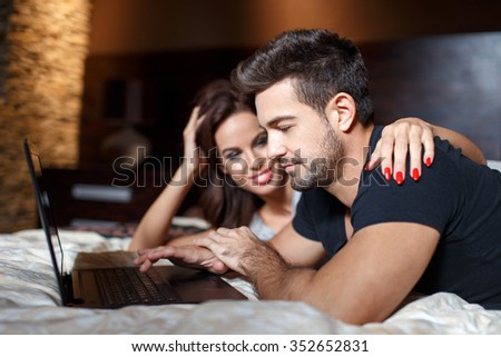 Young couple online shopping on bed by laptop, woman embrace man shoulder #352652831