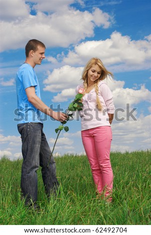 young couple outdoor on green grass. guy granting flower, girl looking shy. blue sky with clouds on background.