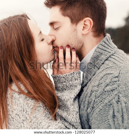 Young couple outdoor portrait. Beautiful pretty girl kissing handsome boy. Sensual photo