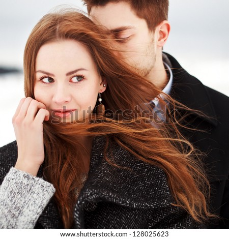 Young couple outdoor sensual portrait in cold windy weather in the field cowered with snow