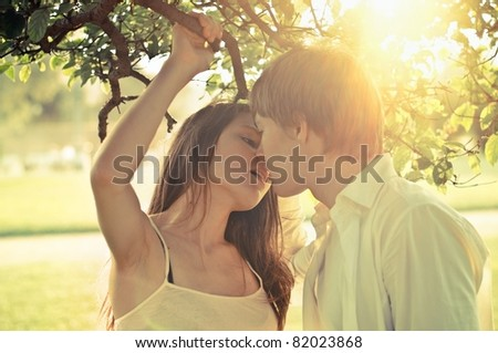 Young couple outdoors, focus on girl's face, shallow DOF
