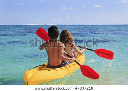 young couple paddles their kayak in a coral bay in hawaii