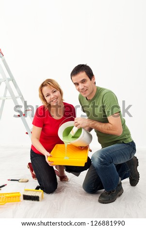 Young couple painting their home - pouring the paint
