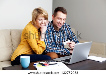 Young couple paying with credit card for online shopping