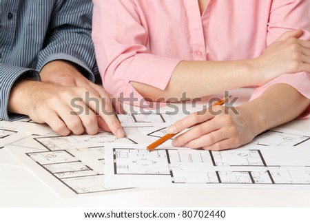 Young couple planning living together in new house with interior blueprints