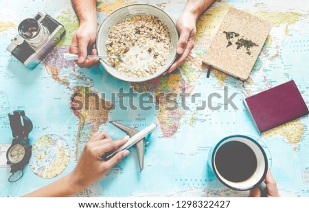 Young couple planning world tour with travel map while doing breakfast - Backpackers people looking for a new countries to explore - Journey trends, globetrotter and holiday concept - Focus on hands