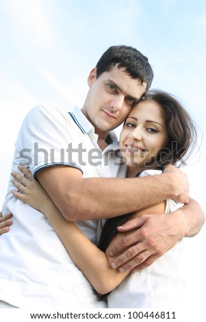 Young couple playing and embrace around in the sky