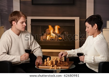 Young couple playing chess at home on a cold winter day.