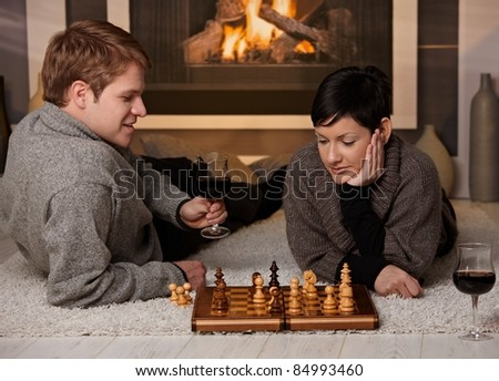 Young couple playing chess at home on a cold winter day.?