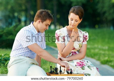 Young couple playing chess outdoors in summer park