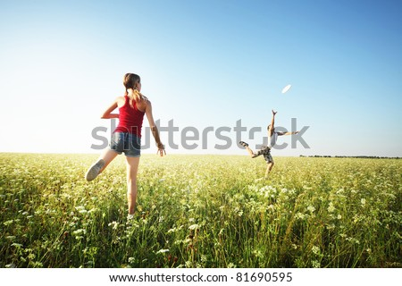 Young couple playing frisbee on a green meadow with grass on clear blue sky background
