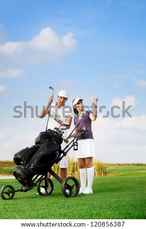 young couple playing golf at the club, choosing  sticks out of the golf-bag
