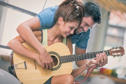 Young couple playing guitar on couch indoor