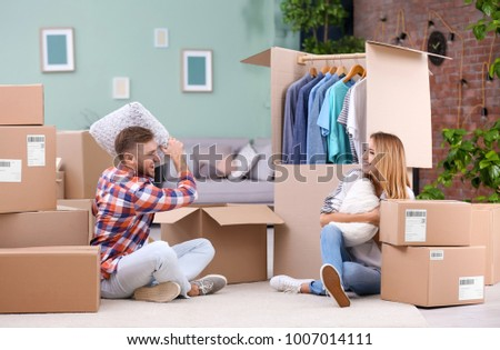 Young couple playing pillow fight near wardrobe boxes on moving day