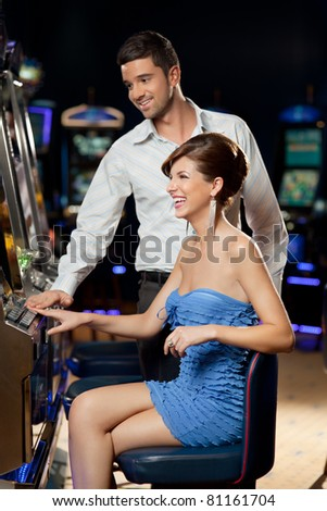 young couple playing together at slot machine