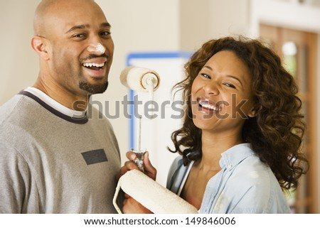 Young couple playing with paint rollers
