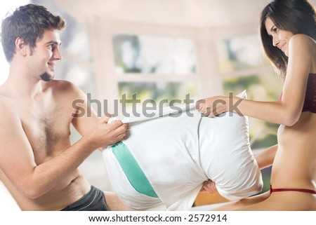 Young couple playing with  pillow on the bed in bedroom