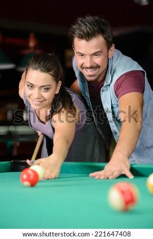 Young couple plays billiards in the dark billiard club