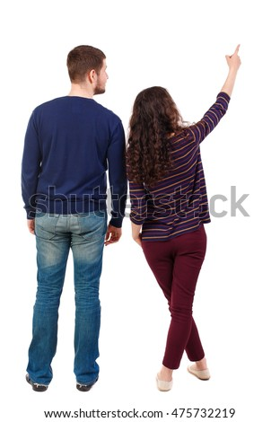 young couple pointing at wal Back view (woman and man). Swarthy girl and a bearded man looking up. #475732219