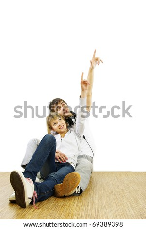 Young couple pointing at wall.