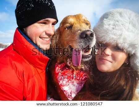 Young couple portrait with winking dog. - stock photo