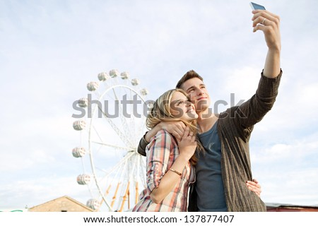 Young couple posing together at an attractions park arcade and using their smartphone to take a picture of themselves smiling.