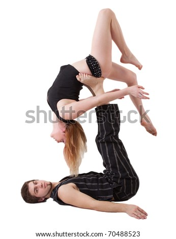 Young couple practices acrobatic balance with woman laying back on man's upstretched legs.