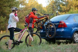 Young Couple Preparing for Riding the Mountain Bikes in the Forest. Unmounting the Bike from Bike Rack on the Car. Adventure and Family Travel Concept.