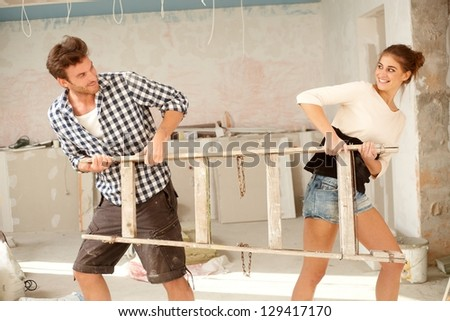 Young couple pulling ladder to opposite directions in house under construction, having fun.