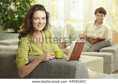 Young  couple reading book sitting on couch in living room. Selective focus on smiling women.