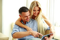 Young couple reading magazine at home