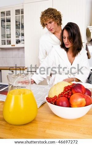 Young couple reading the paper whilst enjoying a healthy breakfast, dressed in bathrobes