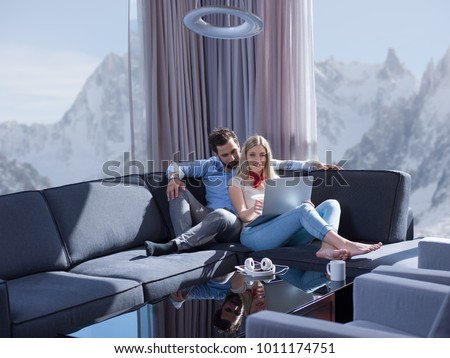 Young couple relaxing at luxury home using laptop computer reading in the living room on the sofa couch.