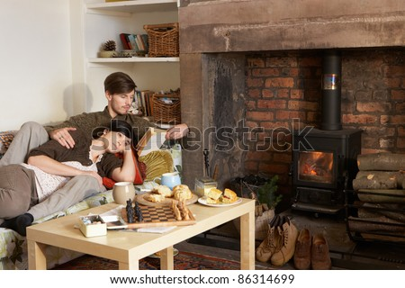 Young couple relaxing by fire