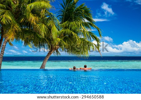 young couple relaxing in infinity pool under coco palms in front of tropical  landscape #294650588
