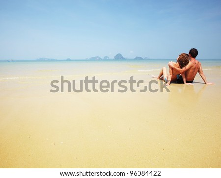 Young couple relaxing on a perfect tropical sand