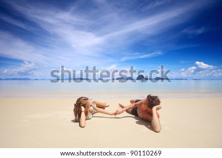 Young couple relaxing on a tropical beach - stock photo